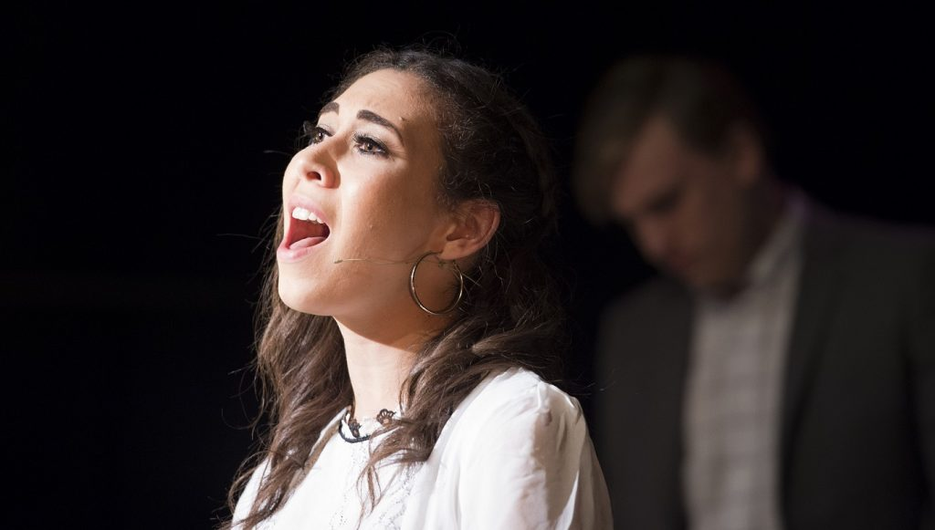 A musical theatre student sings, illuminated by a spotlight.