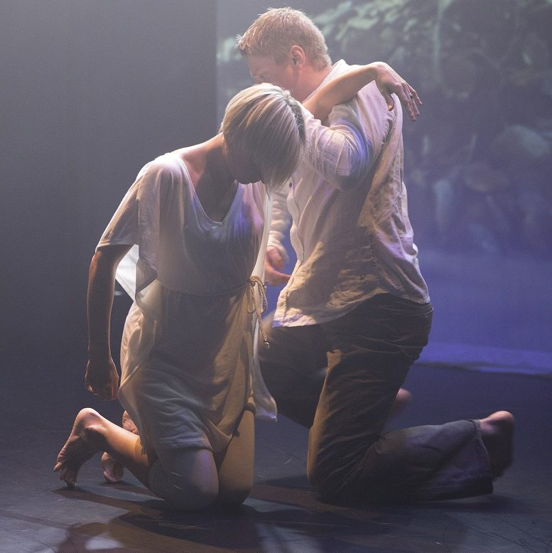Two student dancers support each other under dramatic lighting.
