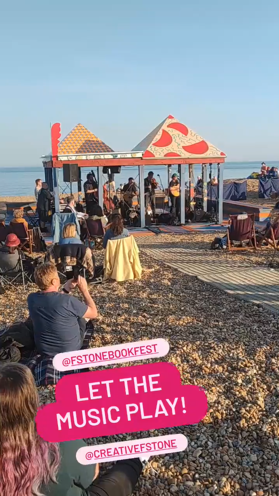 A band playing in a bandstand on a stony beach.