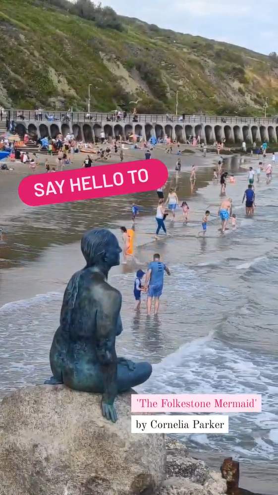The Folkestone Mermaid by Cornelia Parker. A bronze sculpture on rocks beside a beach with families playing in the background.