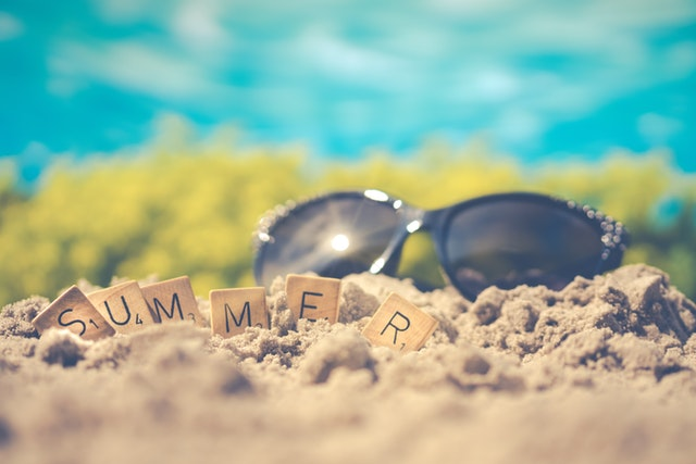 "Sunglasses on beach with ""summer"" spelled out with Scrabble tiles"