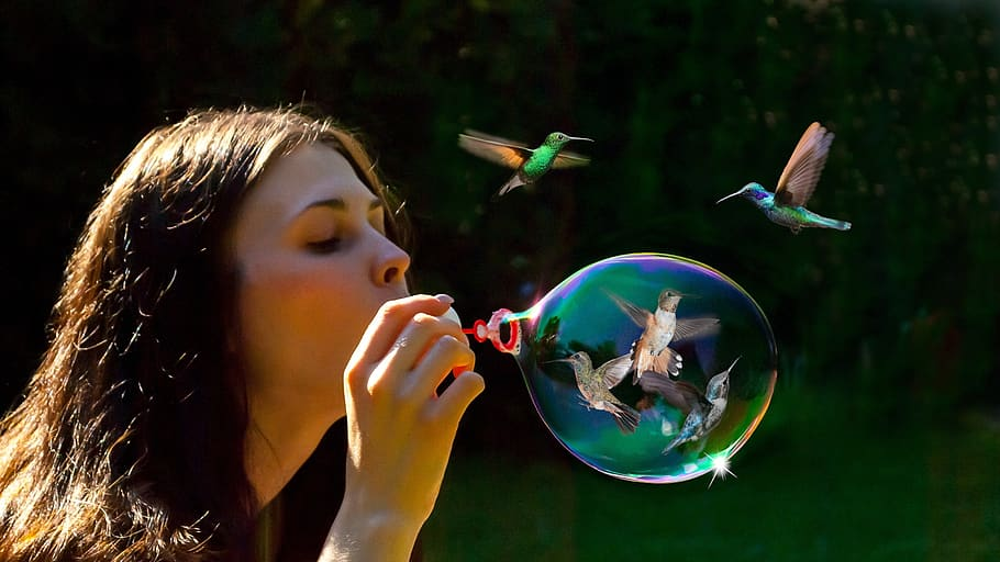 woman blowing bubbles with birds
