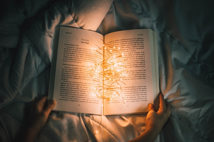 an open book with string lights