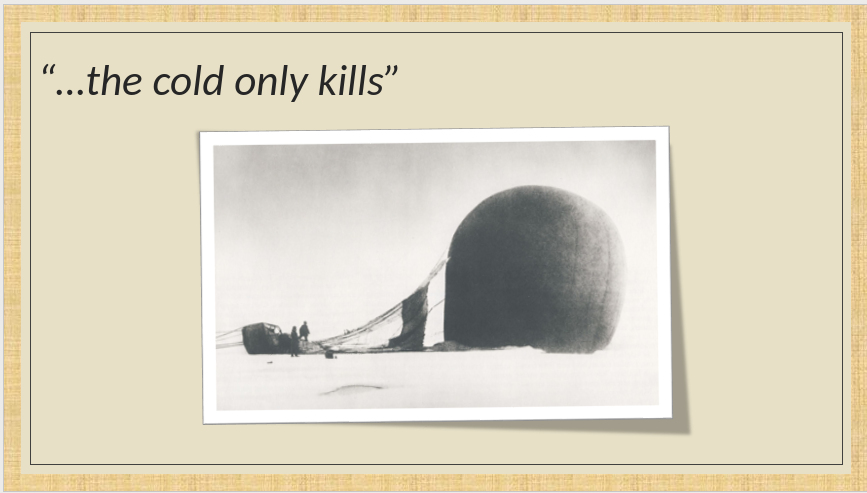 A crashed hot air balloon lying in the snow with men standing next to it.