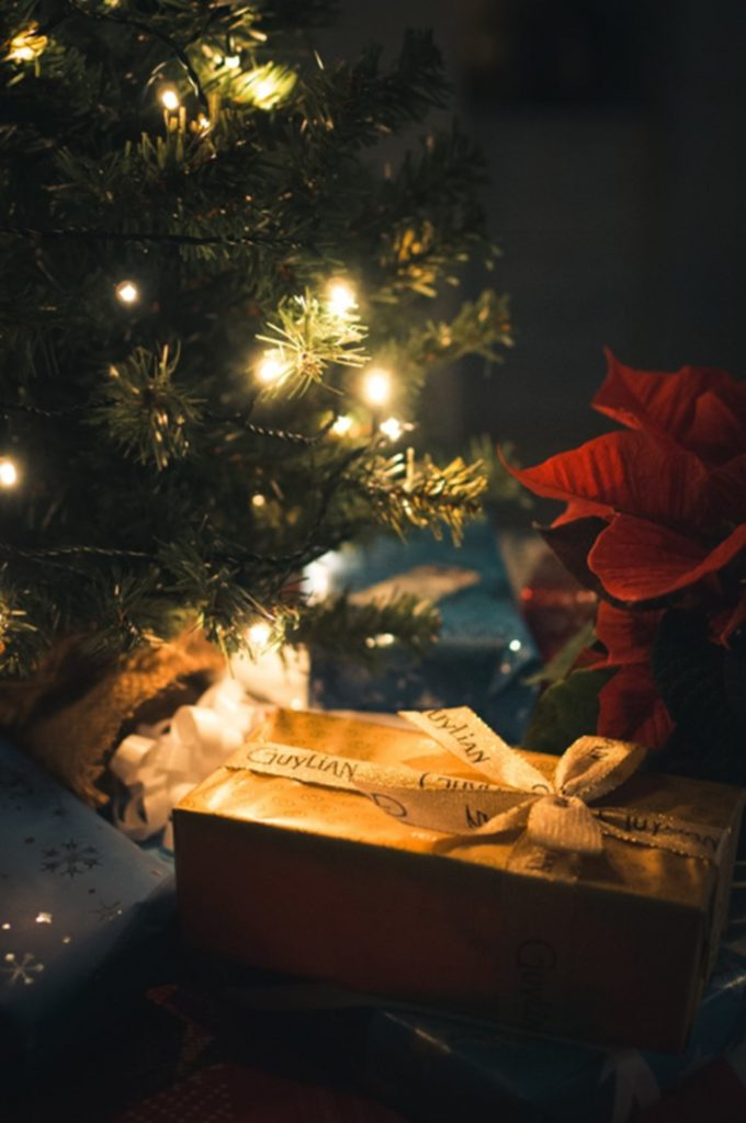 Christmas presents under a Christmas tree with lights