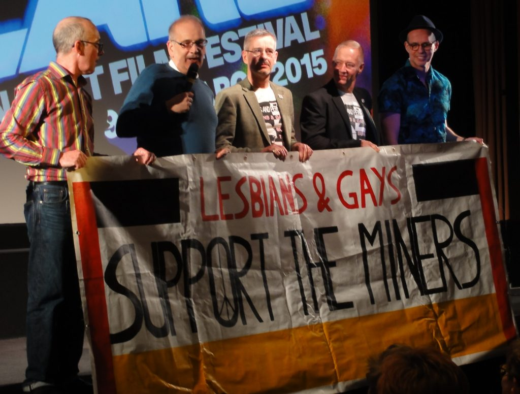 Members of LGSM holding the 1985 LGSM Pride march banner at a film screening of Pride at the BFI.