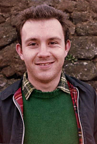 A photograph of a smiling Mark Ashton taken in 1986. He is standing against a brick wall. and wearing a checked shirt, green jumper and navy jacket.