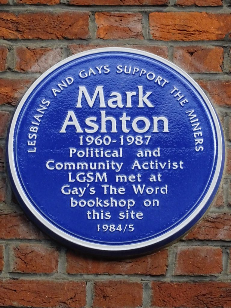 A photograph of the blue plaque at Gay's the Word commemorating Mark Ashton and LGSM. The Plaque reads: Lesbians and Gays Support the Miners, Mark Ashton 1960-1987, Political and Community Activist, LGSM met at Gay's the Word bookshop on this site 1984/5.