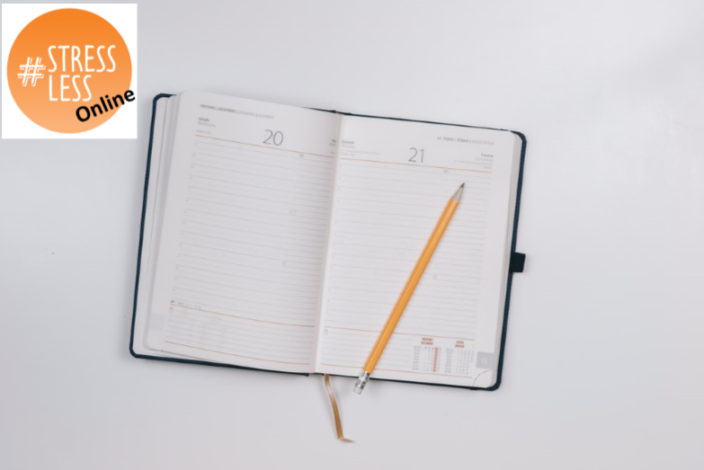 an open diary and pencil on a table top, with the circular stressless logo in the corner