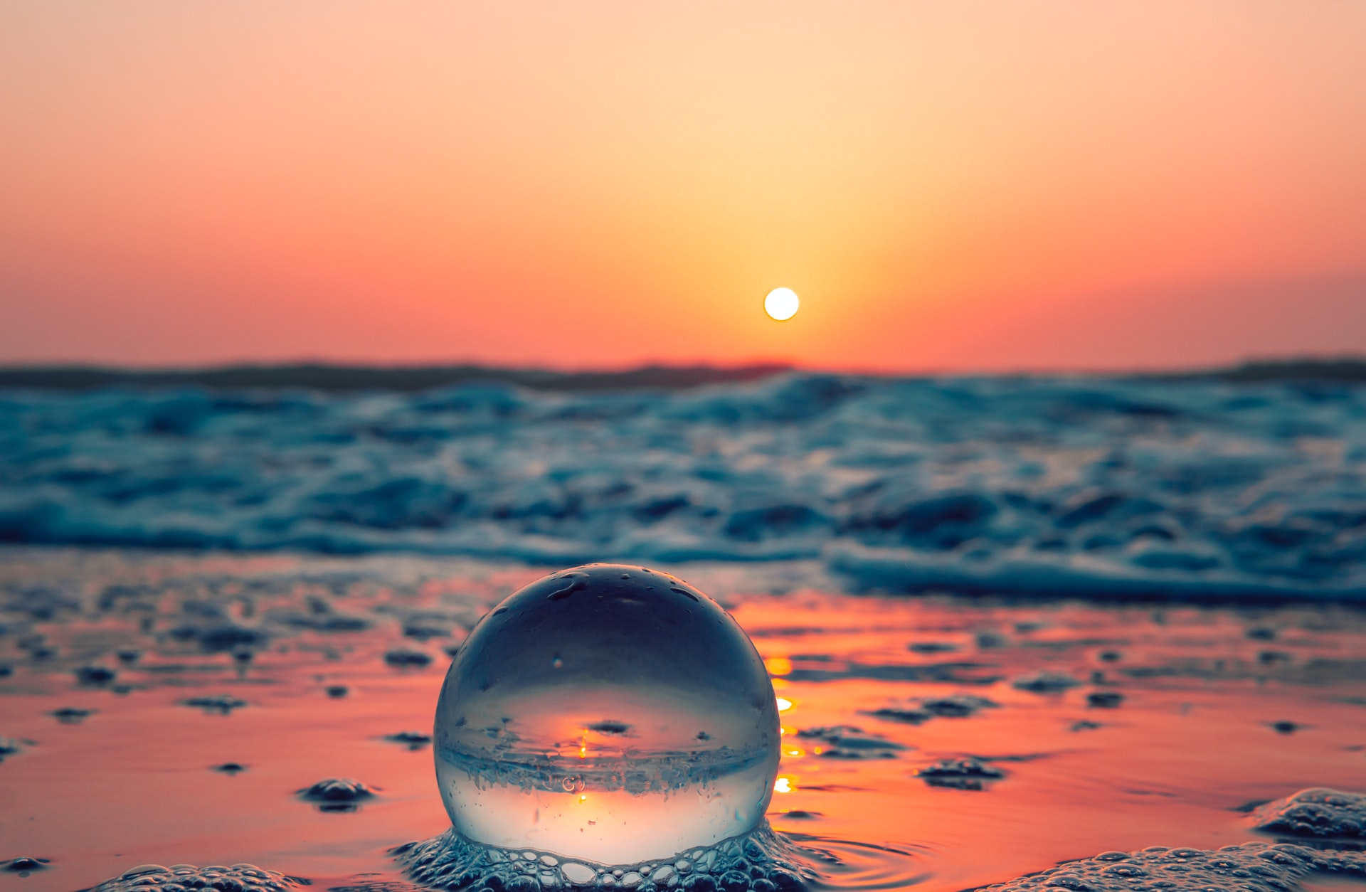 A foamy bubble on the beach, with the ocean in the background and the sun setting