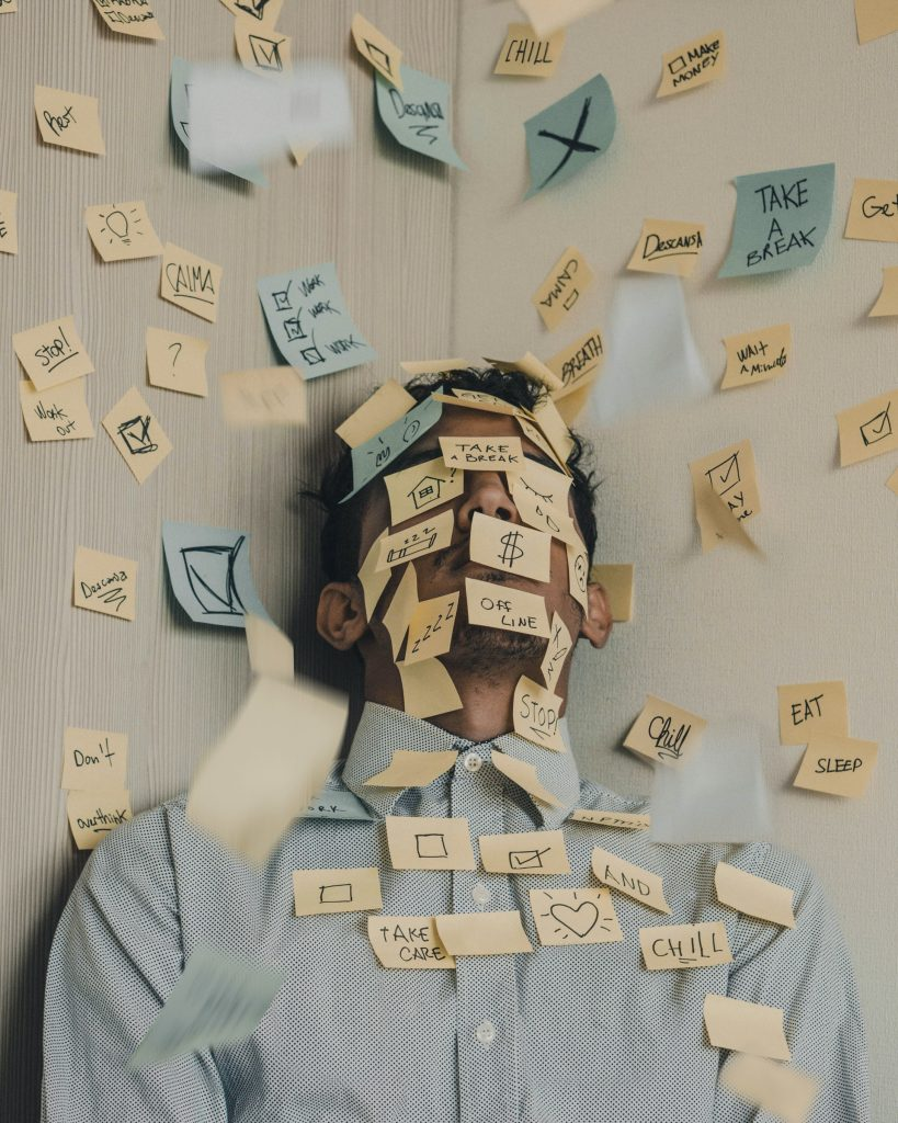An exhausted male covered in post it notes - in front of a wall covered in post it notes
