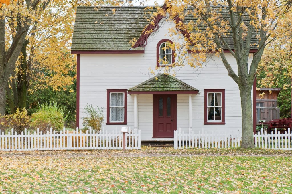white two storey house with a white picket fence