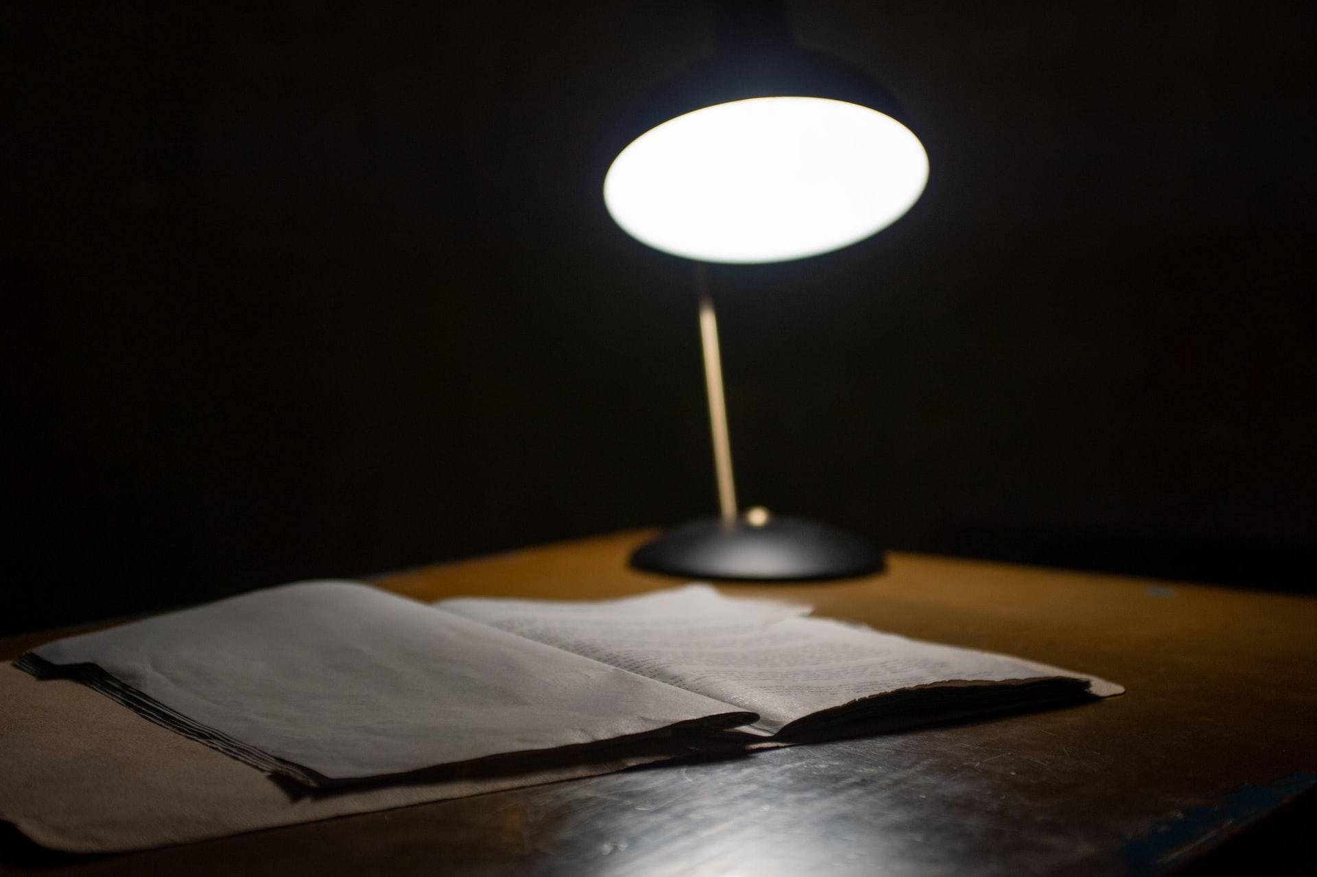 an open book on a desk under a lamp