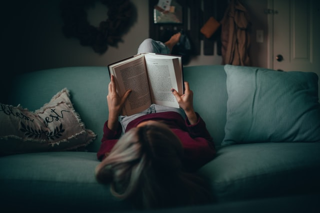 female casually laying on the sofa, upside down, reading a book