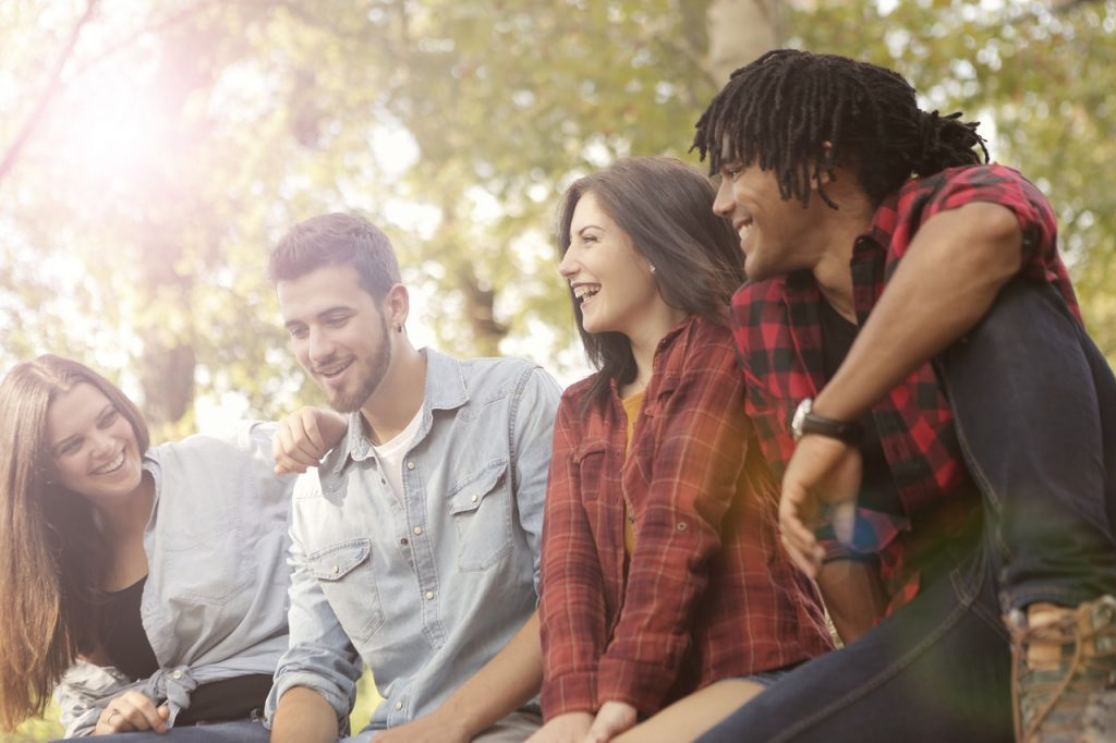 Group of four twenty-something's sitting outside having a laugh and a god time