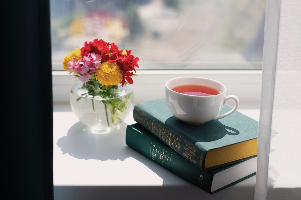 calming window sill view with books, tea and flowers