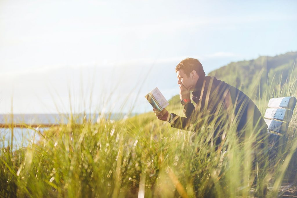 man sitting on a bench in the fields reading a book