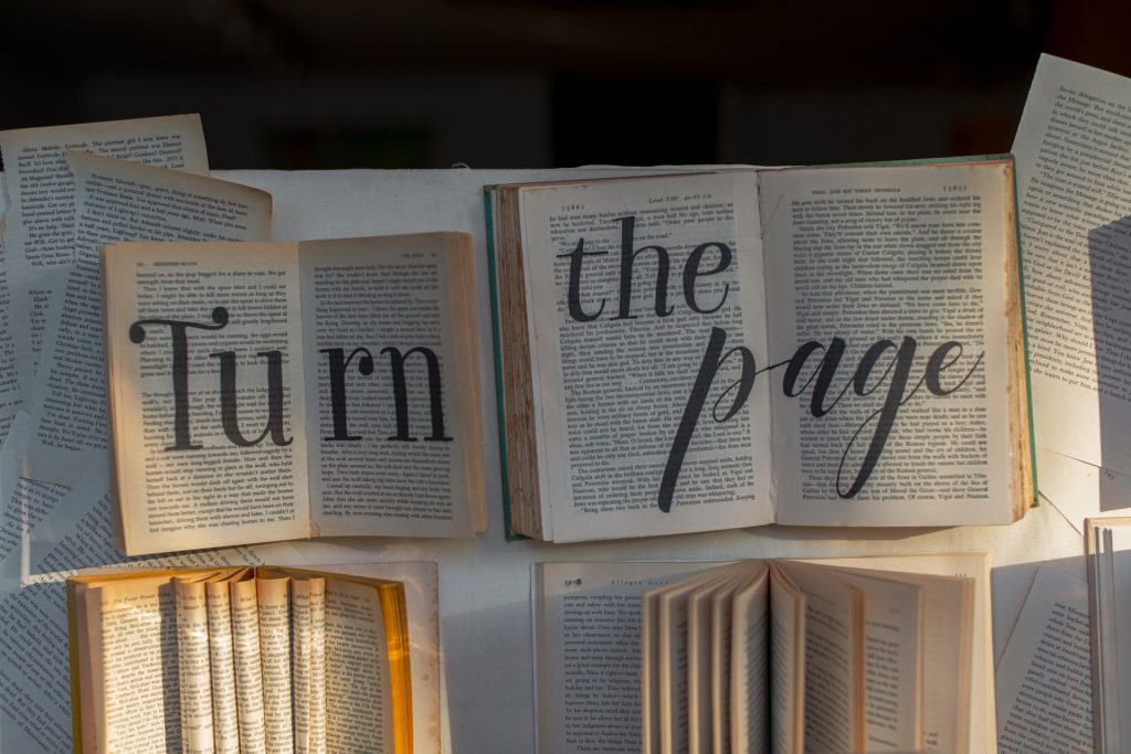 A selection of books with turn the page printed over them