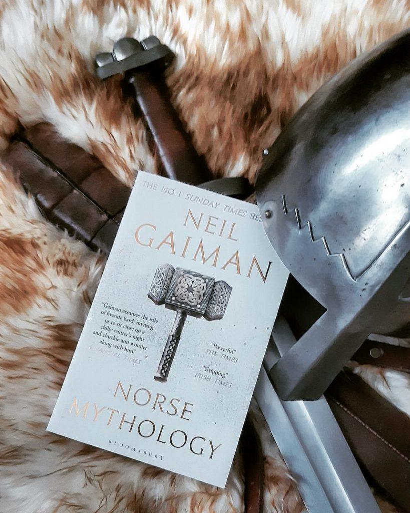 neil gaiman norse mythology book laying on viking furs, swords and helm