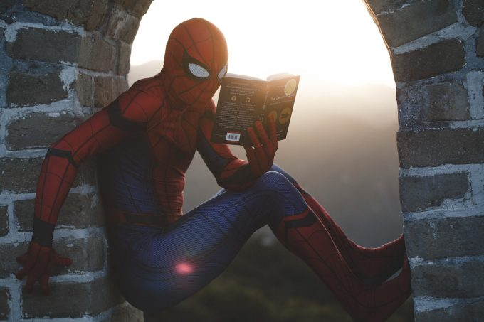 Spiderman sitting high up reading a book