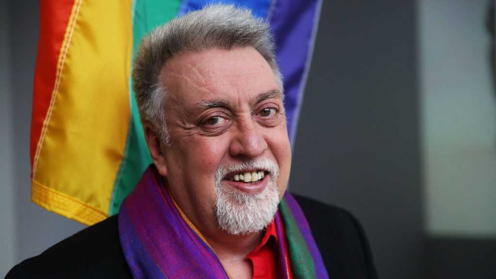 Gilbert Baker with rainbow flag in the background
