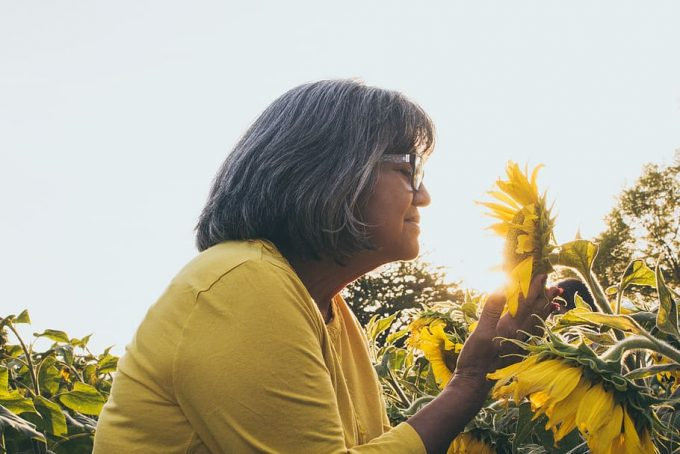 woman-smelling-sunflower