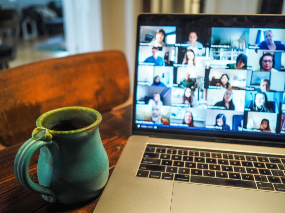 A laptop, with a dozen people logged into a vitural meeting app, set on a wooden table beside a ceramic mug